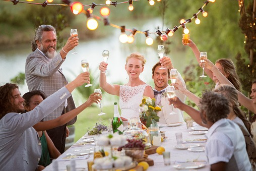 Young couple and their guests toasting with champagne during wedding reception in garden